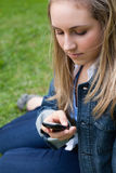 Young girl sending a text while sitting on the grass Stock Photography