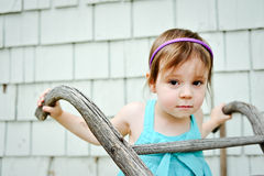 Young girl with serious face. Young 3 year old girl making serious face with pushing wheel barrow Royalty Free Stock Photography