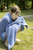 Young girl seven years old wraping in towel. Sitting on  river bank Stock Photos