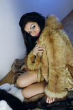 Young girl with several natural fur coats Stock Photography