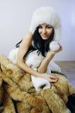 Young girl with several natural fur coats Stock Photos