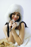 Young girl with several natural fur coats Stock Images