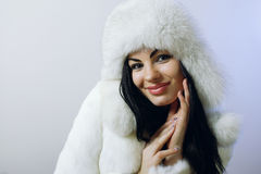 Young girl with several natural fur coats Royalty Free Stock Images