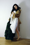 Young girl with several natural fur coats Royalty Free Stock Image