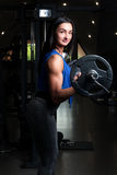 Young girl with sexual inflated figure, in the gym, standing rai. Ses the bar on biceps Stock Photography