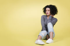 Young girl with sexy look sitting on isolated yellow background. Royalty Free Stock Images
