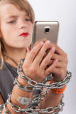 Young girl shackled with a chain using smartphone Stock Photography
