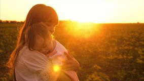 Young girl shakes little baby in glare of setting sun. Silhouette mother and child. Kid sleeping in arms of my mom stock video footage