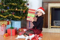 Young girl shaking christmas gift Royalty Free Stock Photo