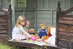 Young girl in shed with baby playing tea Royalty Free Stock Images