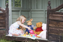 Young girl in shed playing tea and smiling Royalty Free Stock Photos