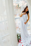 Young girl in sheet with rose posing near window Royalty Free Stock Photography