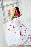 Young girl in sheet with rose posing near window Stock Photos