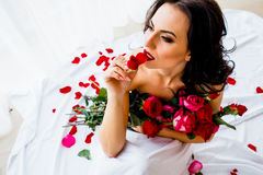 Young girl in sheet with rose posing Stock Photo