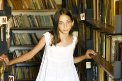 Young girl between shelves of old library Royalty Free Stock Photo
