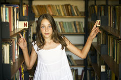 Young girl between shelves of old library Stock Images
