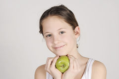 Young girl with a shiny green apple Stock Image