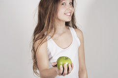Young girl with a shiny green apple. Studio shot with a teenager girl offering a nice green apple Royalty Free Stock Photo