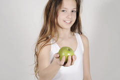 Young girl with a shiny green apple. Studio shot with a teenager girl offering a nice green apple Royalty Free Stock Images