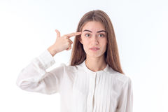 Young girl in shirt keeps finger Temple isolated on white background Royalty Free Stock Images