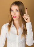 Young girl in shirt lifts a finger up Stock Images