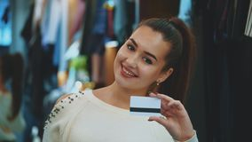 Young girl in shop with shopping and credit card.