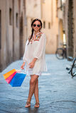 Young girl with shopping bags on narrow street in Europe. Portrait of a beautiful happy woman holding shopping bags Stock Photography