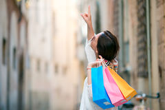 Young girl with shopping bags on narrow street in Europe. Portrait of a beautiful happy woman holding shopping bags Royalty Free Stock Photos