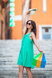 Young girl with shopping bags on narrow street in Europe. Portrait of happy woman holding shopping bags Royalty Free Stock Images