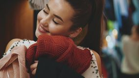 A young girl is shopping at the store. Found things that suit her. Enjoying a soft cloth. Embracing sweaters stock video footage