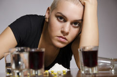 Young girl short hair addicted to drugs. Alcohol and pills. Looking at camera, selective focus on girl, gray background. Struggling with her problems royalty free stock image