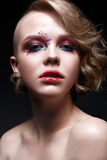 A young girl with a short haircut and bright creative makeup. A beautiful model with sparkles on the face and red lips. Royalty Free Stock Photos