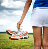 Young girl in shorts holding her sneakers Stock Photo