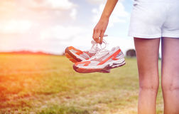 Young girl in shorts holding her sneakers royalty free stock photos