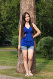 Young girl in shorts leaned against a tree in the Park Stock Image
