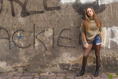 Young girl in shorts and sweater standing near the wall in old city. Royalty Free Stock Images