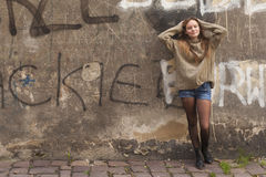 Young girl in shorts and sweater standing near the wall in old city. Cute trendy young girl in shorts and sweater standing near the wall in old city Royalty Free Stock Photos