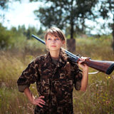 Young girl with a shotgun looks into the distance in an outdoor Stock Images