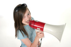 Young Girl Shouting Through Megaphone 5. Young pre teen or tween girl shouting, speaking, or singing through a megaphone. Shot on white royalty free stock photo