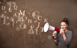Young girl shouting into megaphone and text come out Stock Photography