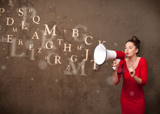 Young girl shouting into megaphone and text come out. Young girl shouting into megaphone and abstract text come out Stock Images