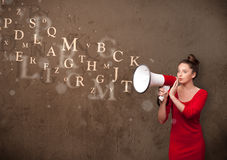 Young girl shouting into megaphone and text come out Royalty Free Stock Photography