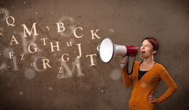 Young girl shouting into megaphone and text come out Royalty Free Stock Images