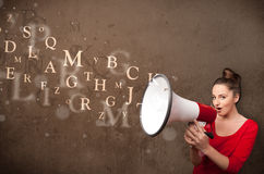 Young girl shouting into megaphone and text come out Royalty Free Stock Image