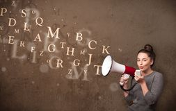 Young girl shouting into megaphone and text come out Stock Images
