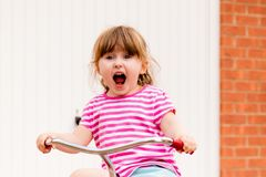 A young girl shouting while riding a bicycle royalty free stock photo