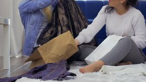 Young girl show a new dress to her friend after shopping. Two young girls sits on floor at home after shopping among bags with purchases. The friends discussing stock footage