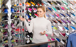 Young girl showing an assortment of the shoes in the store Royalty Free Stock Photography