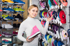 Young girl showing an assortment of the shoes in the store Stock Photo