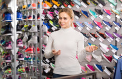 Young girl showing an assortment of the shoes in the store. Cheerful young spanish girl showing an assortment of the shoes in the store stock images
